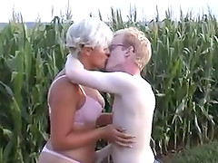 Lustful blond milf has sex with a young dude in a field