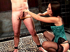 Lingerie-clad dominatrix with long dark hair torturing a stranger
