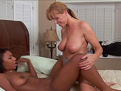 Ebony vixen being pounded with a strap on dildo in hot interracial lesbian action