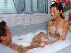 Amazing Asian masseuse stroking a white dude's cock in the tub