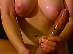 Dark haired mature MILF oils up a huge cock and strokes it